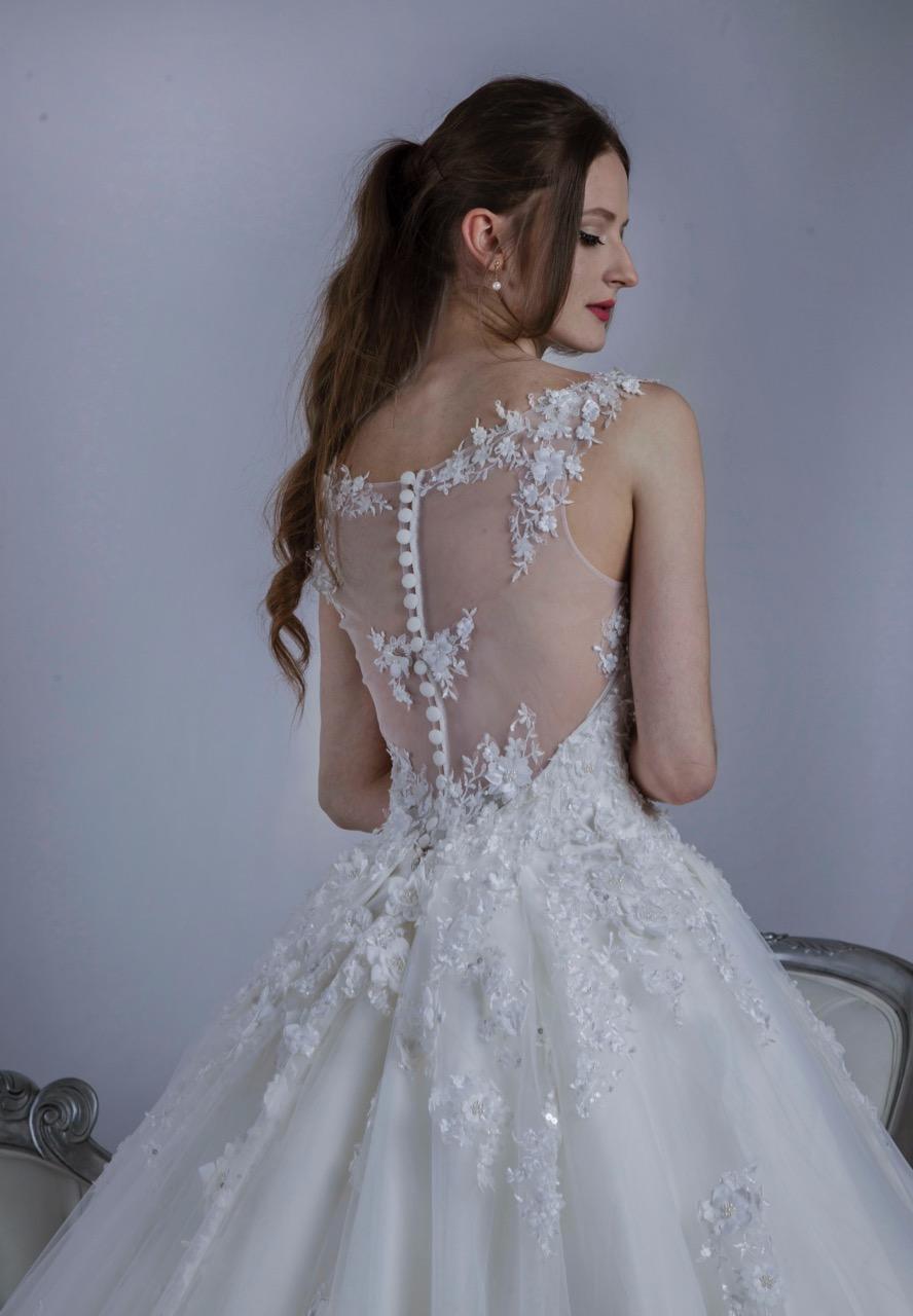 Dos d'une robe de mariée à boutons et ornement de dentelle